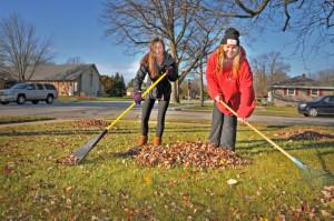 Sarah Shepherd and Brooke Porter (l-r) both juniors at MFHS and members of the Junior Optimist Club raked in a yard along Menomonee Avenue.